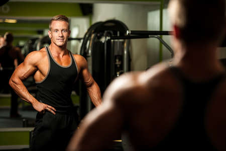 Handsome man looking in mirror after body building workout photo