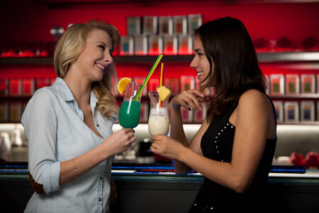 Two beautiful women drinking cocktail in a night club photo