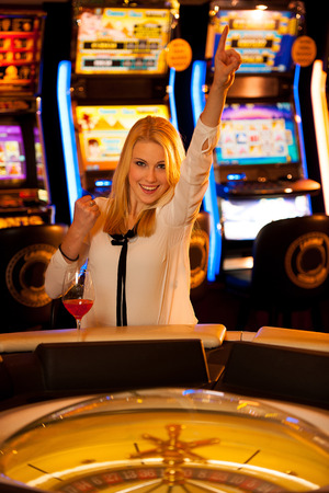 Young blond woman playing roulette in casino and winning photo