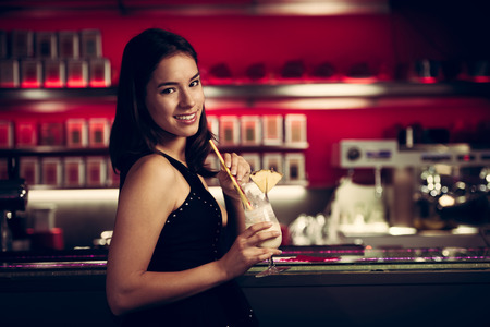 preety: preety young woman drinks cocktail in a night club Stock Photo