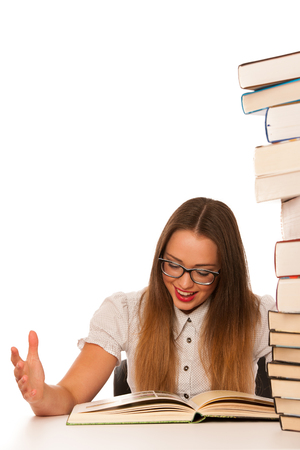 Happy asian caucasian girl lerning in study woth lots of books on the table isolated photo