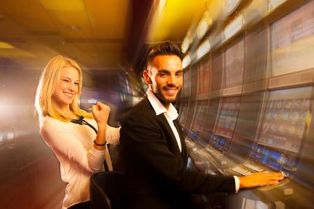 tragamonedas: pareja ganadora en la m�quina tragaperras en el casino Foto de archivo