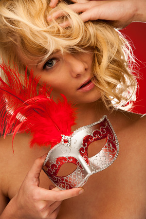 beauty portrait of Beautiful young blonde woman with venice carnival mask in hands over red photo