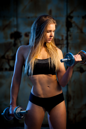 area sexy: attractive young woman working out with dumbbells - bikini fitness girl with healthy lifestyle and perfect body Stock Photo