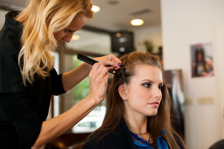 dry hair: Young woman in hairdresser saloon having a haircut Stock Photo