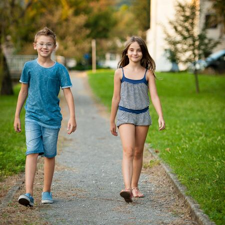 Young teenage boy and girl walk in park in the city