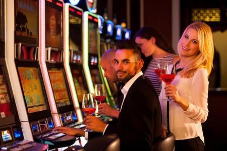 若い人たちのカジノでの演奏のスロット マシン 写真素材