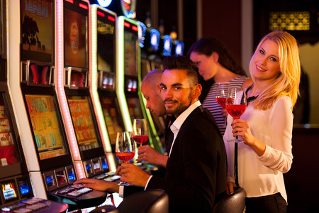 Les jeunes jouant aux machines à sous dans le casino Banque d'images - 35656504