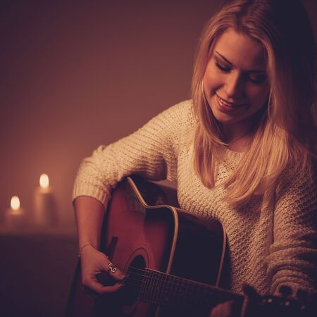 Young blonde woman playing guitar in candle light photo