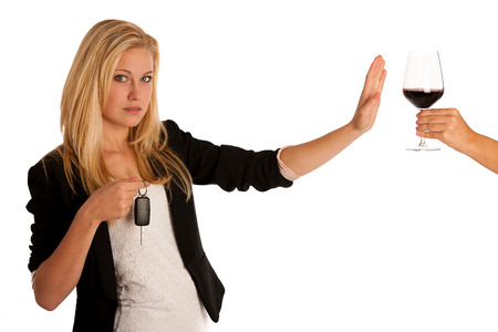 beautiful blond woman gesturing dont drink and drive gesture, with refusing a glass of red wine isolated over white