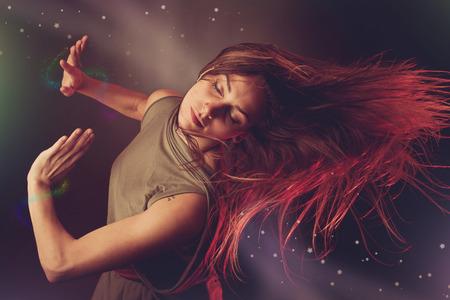 Mooie vrouw danser dansen over donkere achtergrond met lichtstralen en ster wervelingen en glitters