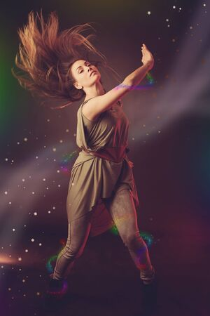 Beautiful woman dancer dancing over dark background with light rays and star swirls and glitters photo