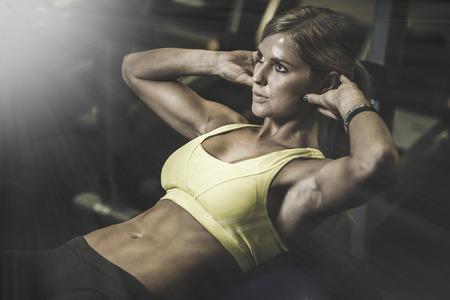 gimnasio mujeres: hermosa mujer atl�tica trabajando intervalos abdominales en el gimnasio