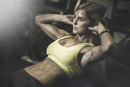 muskeltraining: sch�ne sportliche Frau arbeitet ab Abst�nden in Fitness-