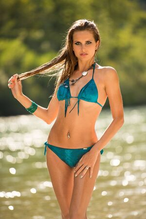 preety: Preety woman in swimsuit near alpine river in early summer afternoon Stock Photo