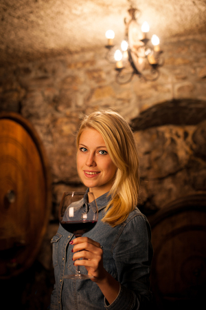 Beautiful young woman tasting red wine in a wine cellar photo