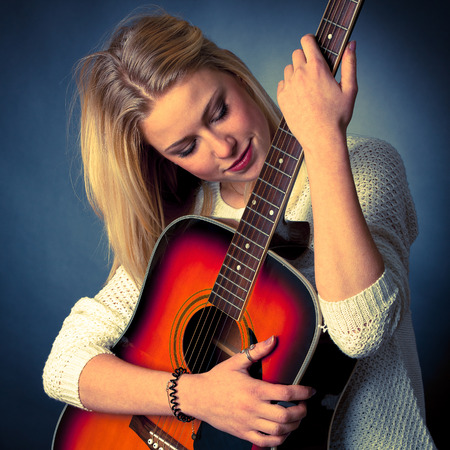 woman guitar: studio Portrait of young blonde guitar player Stock Photo