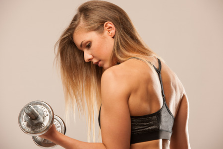 attractive young woman working out with dumbbells - bikini fitness girl with healthy lifestyle and perfect body Stock Photo