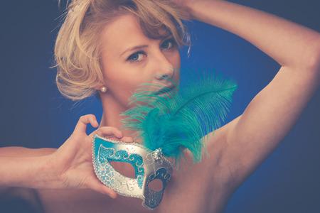 ojos azules: Retrato de la belleza de la mujer hermosa joven rubia con m�scara de carnaval de Venecia en las manos sobre fondo azul