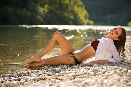 Preety woman in swimsuit near alpine river in early summer afternoon Stock Photo