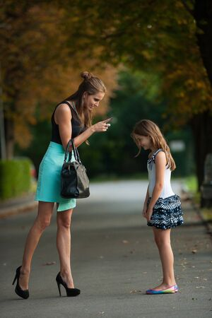 naughty girl: Mother talking to naughty girl on a street in park