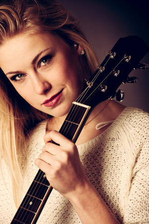 studio Portrait of young blonde guitar player photo