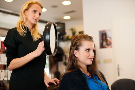Young woman in hairdresser saloon having a haircut photo