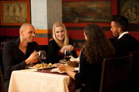 bebiendo vino: Los jóvenes comen la cena en el restaurante