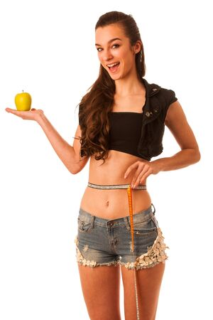 Healthy female body with apple and measuring tape. Healthy fitness and eating lifestyle concept. photo