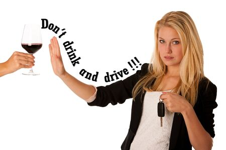 beautiful blond woman gesturing don\t drink and drive gesture, with refusing a glass of red wine isolated over white