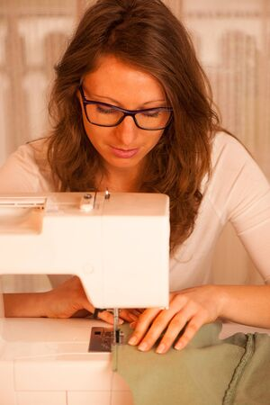 beautiful Dressmaker woman working with sewing machine photo
