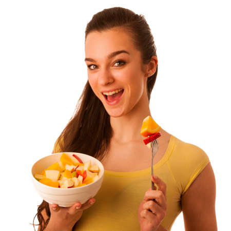 Beautiful happy asian caucasian woman in yellow t shirt eating fruit salad as a healthy lifestyle concept isolated over white photo