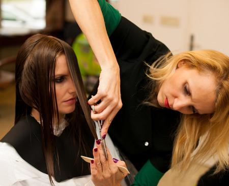 tratamiento capilar: Peluquer�a haciendo que el tratamiento del pelo a un cliente en el sal�n Foto de archivo
