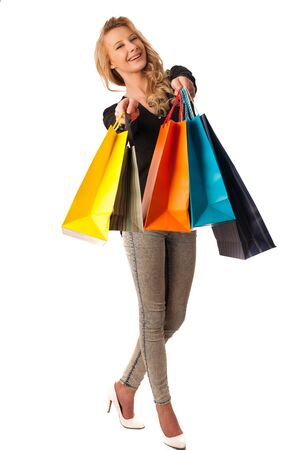 Beautiful young blonde caucasian woman holding vibrant shopping bags in her hands - consumerism photo