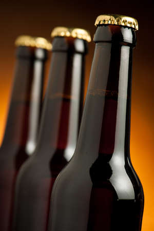 brown bottles: Three brown bottles of beer standing in row on orange background. Stock Photo