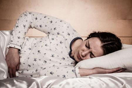 Mujer caucásica asiática con dolor en su stomcah