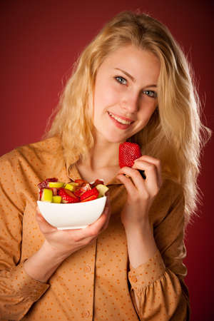 Beautiful young caucasian blonde woman holds a delicious fruit salad as a sign for healthy eating over red photo