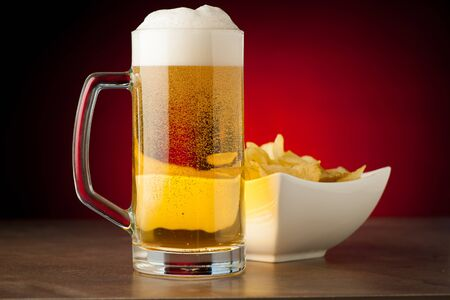 potatoe: bottle, glass of beer and potatoe chips on stone table over red background