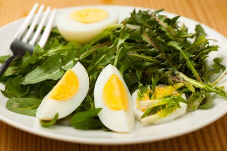 Fresh spring green  dandelion salad with eggs on a plate closeup