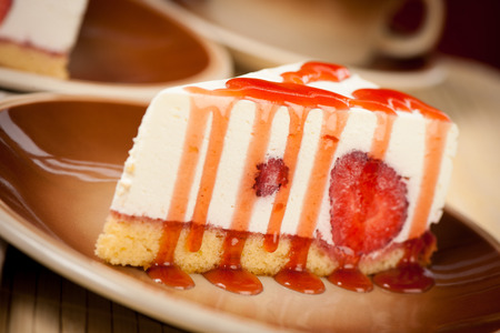 cip: A slice of delicious cheeese cake with strawberries and syrup served on a table