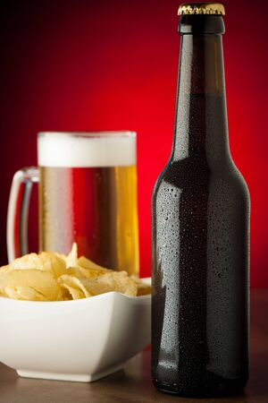 bottle, glass of beer and potatoe chips on stone table over red background photo