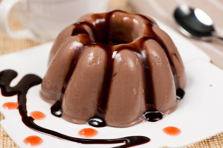 blancmange: Chocolate pudding with chocolate dressing on white plate Stock Photo