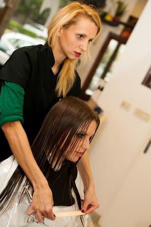 cut hair: Hairdresser making hair treatment to a customer in salon