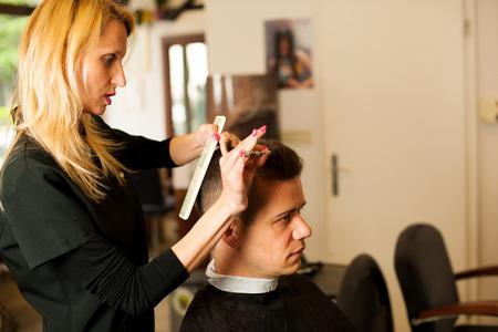 salon de belleza: El corte de pelo de la sonrisa de cliente hombre en un salón de belleza femenino del peluquero Foto de archivo