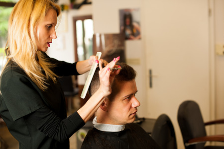 beauty shop: Female hairdresser cutting hair of smiling man client at beauty parlour