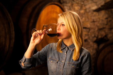 wine tasting: Beautiful young woman tasting red wine in a wine cellar Stock Photo