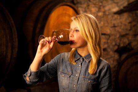 Mooie jonge vrouw proeverij rode wijn in een wijnkelder
