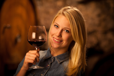 Beautiful young woman tasting red wine in a wine cellar Stock Photo