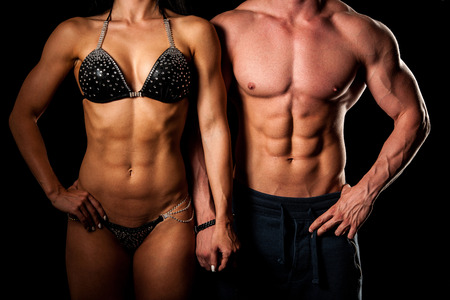 tummy: Fitness couple poses in studio - fit man and woman