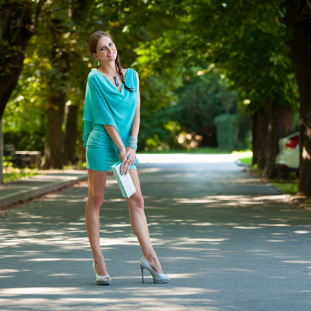 turquise: Blog style beautiful brunette woman in fashionable dress posing in park presenting garment Stock Photo